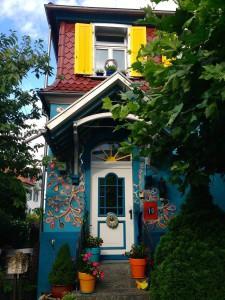 """Sehen wir uns nur den Eingang an. Die Stufen dahin bilden das hohe Bewusstsein der Hausbesitzerin ab. Die entsprechende Dreiecksform (Dreieck: Erkenntnis) finden wir auch am Vordach. Wir sehen über dem Eingang eine strahlende Sonne, die einladende Wärme ausstrahlt und optimistisch stimmt. Entsprechende Bogenformen, die die """"Leichtigkeit des Seins"""" symbolisieren, sind am Eingang ebenfalls vorhanden. Das verspielte Mosaik und die liebevolle Bepflanzung sind das perfekte Yin gegenüber den geraden Yang-Linien und den klaren Farben."""
